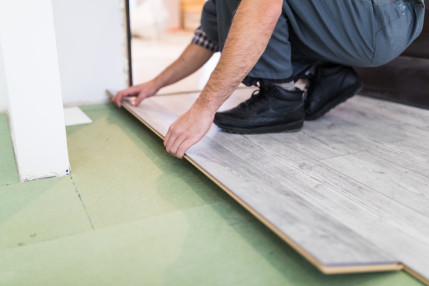 worker-processing-floor-with-laminated-flooring-boards_231208-4211